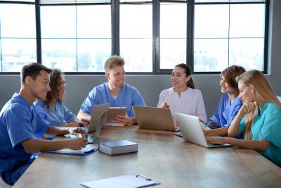 group of smart medical students with gadgets in college